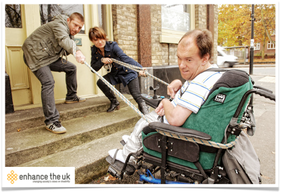 a wheelchair user being 'helped' up some stairs
