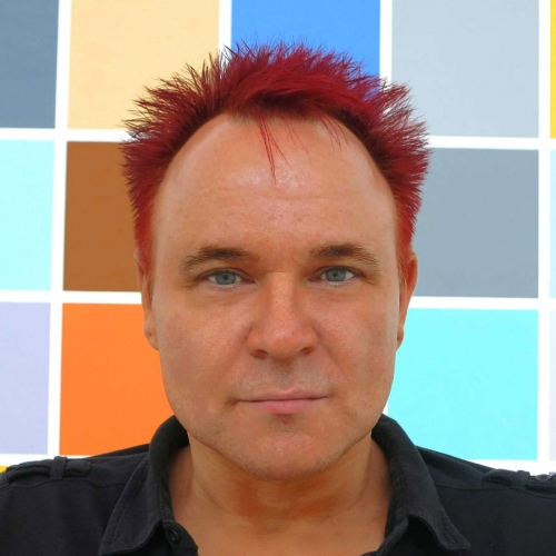 Mik looking directly into the camera, with red spikey hair and a coloured grid pattern behind him