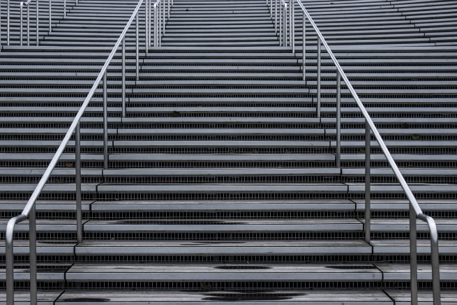Image of grey stairs with silver handle bar representing the career ladder