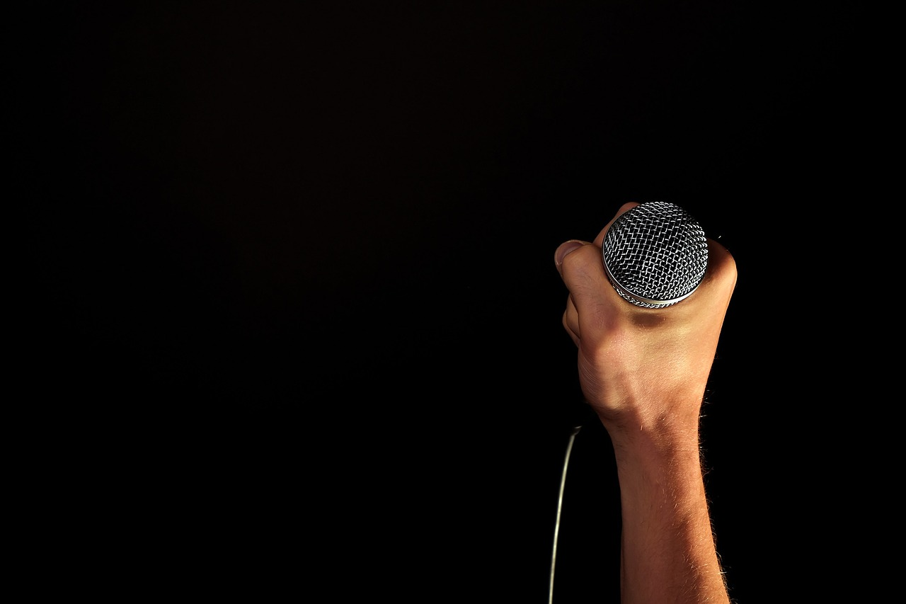 A man's hand holding a microphone with a black background