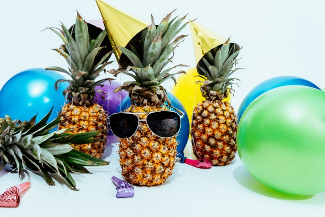 pinapples party hats, balloons and party poppers