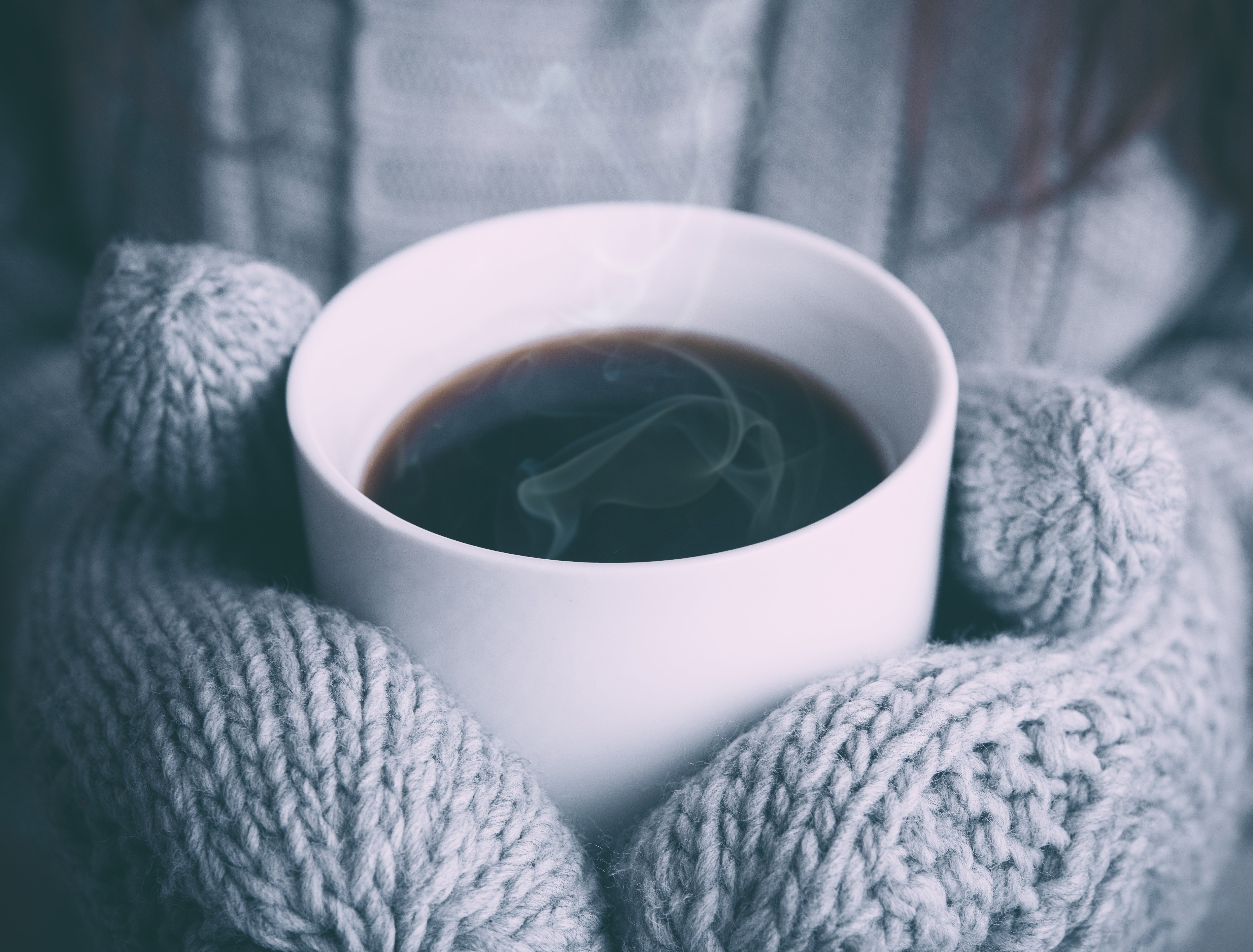 A steaming hot mug of coffee held by someone wearing knitted grey mittens