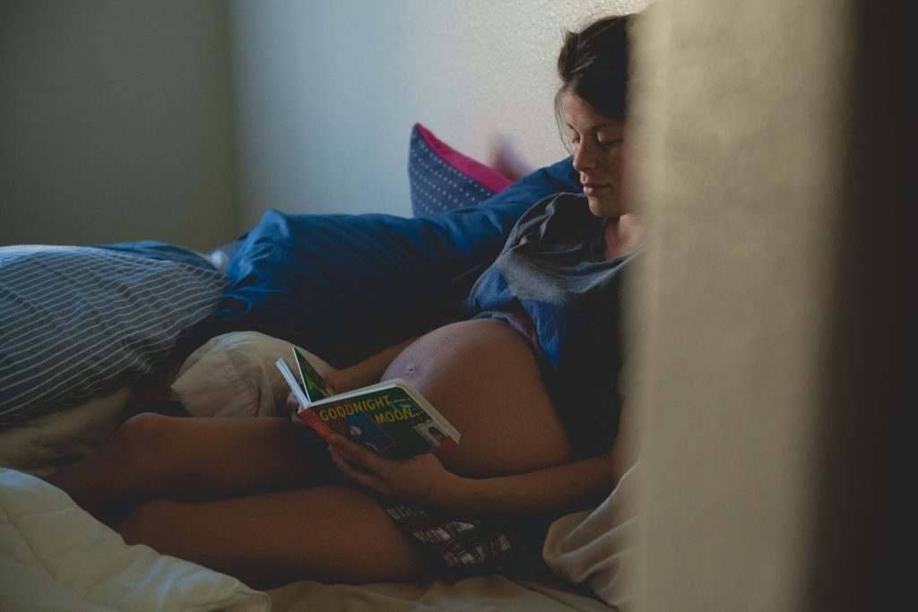 A heavily pregnant woman sitting on a bed reading a book
