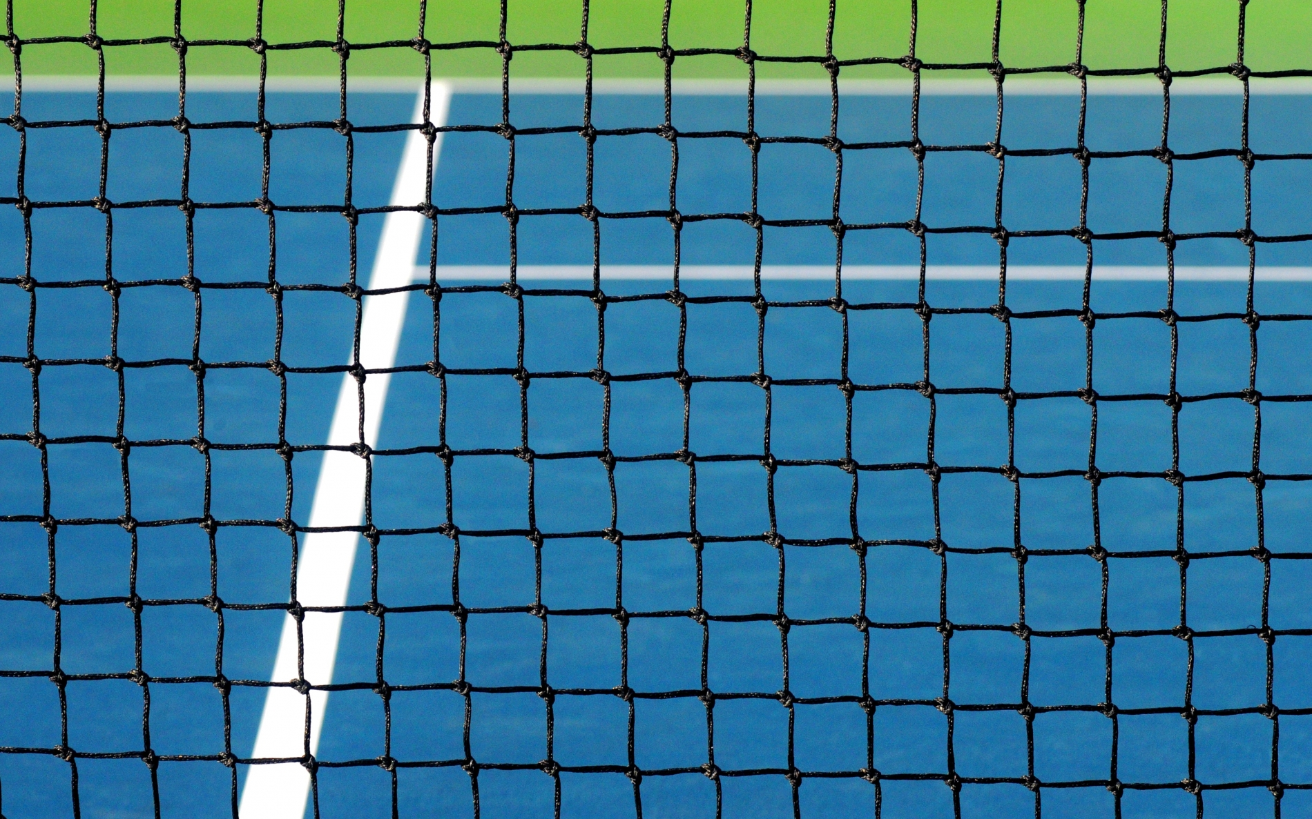 A blue tennis court with white lines looking through the black netting