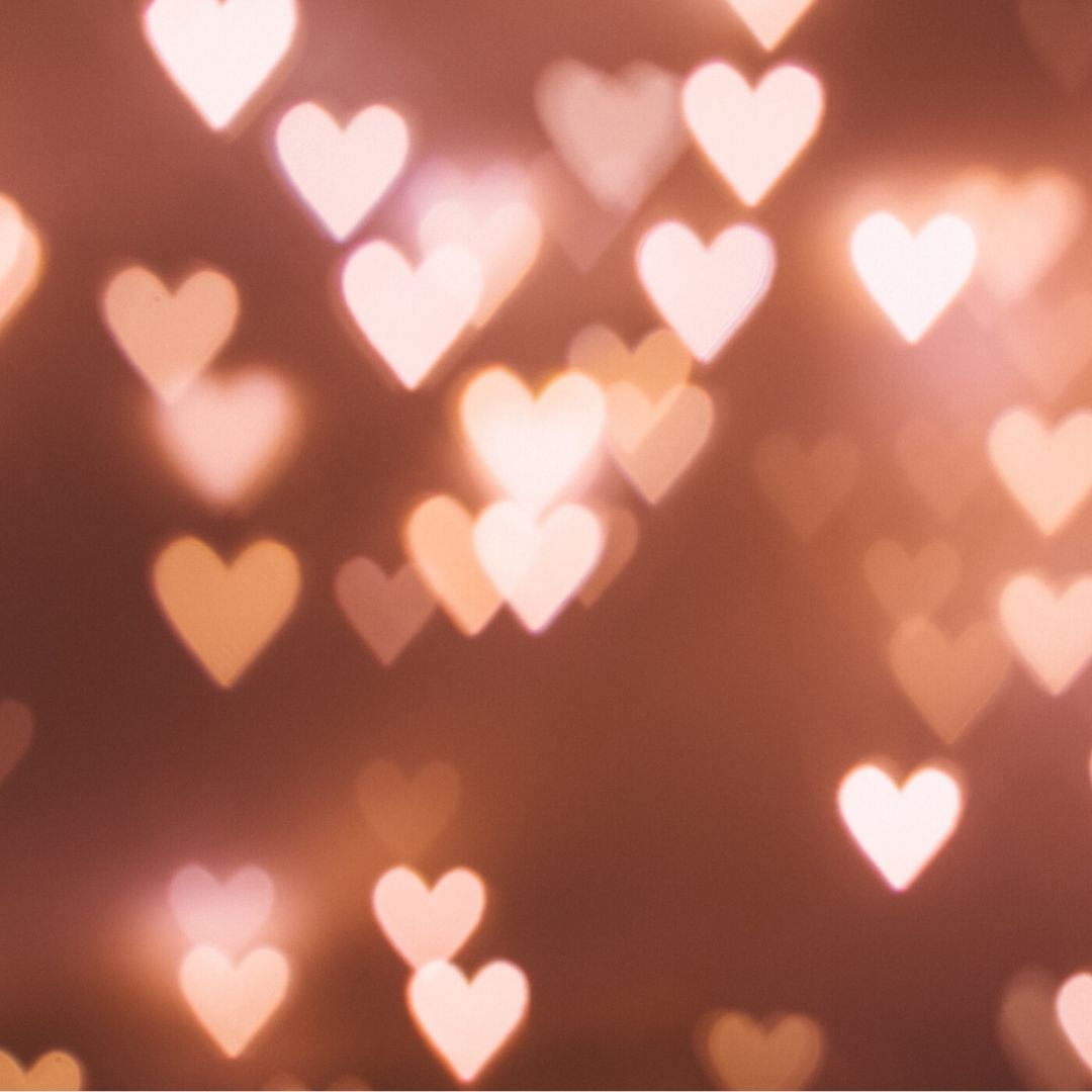 there are lots of white and pale pink hearts glowing against a dusky pink background