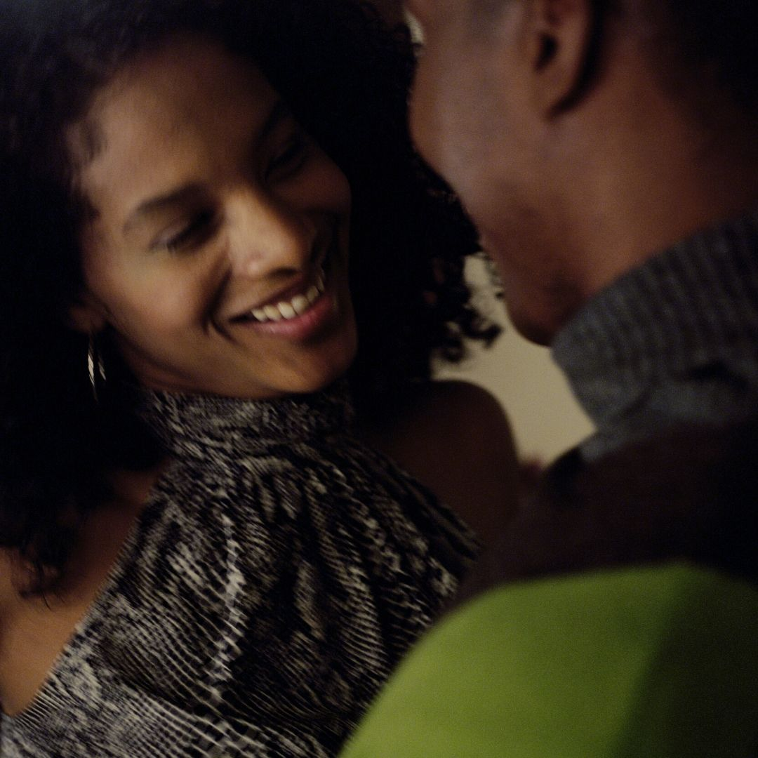 A man and woman are standing close and smiling. The woman has black curly hair and a grey halter top, the man has a jumper with a grey neckand green shoulders.