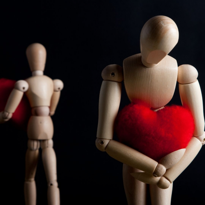 Two wooden dummies moving away from each other carrying a bright red heart