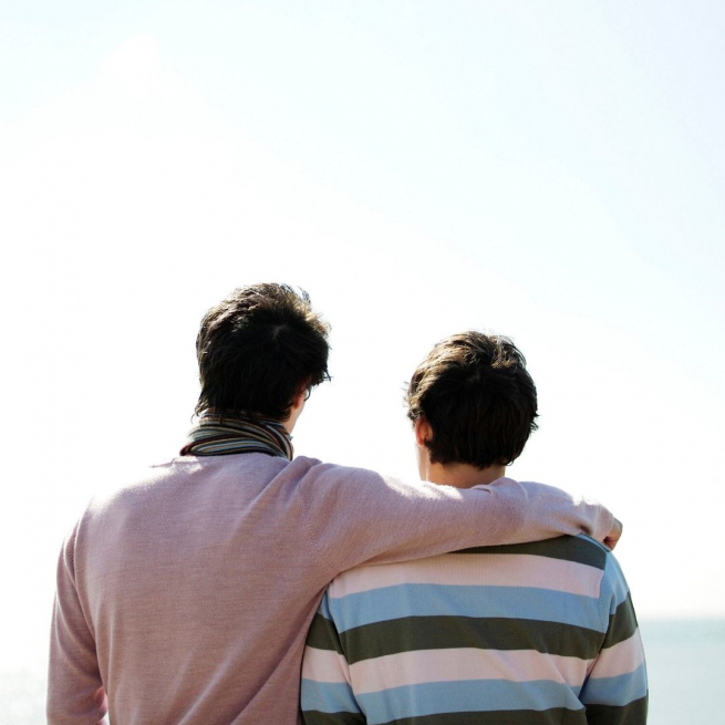 Two men looking out at the ocean with their backs to the camera, the taller one has his arm around his partner