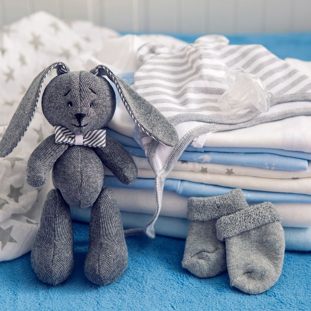 A grey toy rabbit resting against a pile of baby clothes