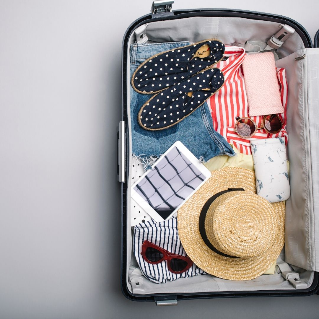 An open trolley case with a hat, sunglasses, striped red top, jeans and polka dot shoes