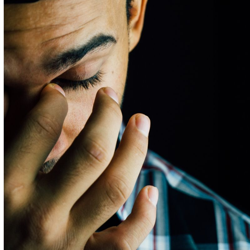 A man holds his hand to his face, his eye is closed and he looks down with a sad expression