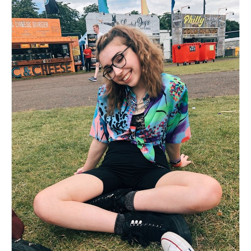 Georgia is sitting on the grass cross legged at a festival. She is wearing a pink,green and vibrant blue shirt with black shorts and boots. She is smiling and her brown shoulder length hair is wavy.