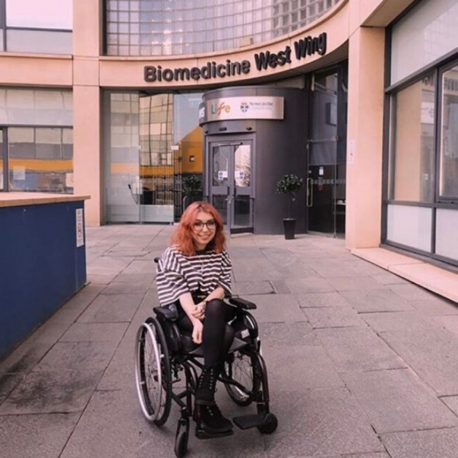Georgia is sitting in her wheelchair in front of the hospital entrance. She's got dyed red hair, glasses and a big smile. She is wearing a baggy black and white striped t-shirt with black skirt and boots. Biomedicine West Wing is written in letters above the hospital entrance.