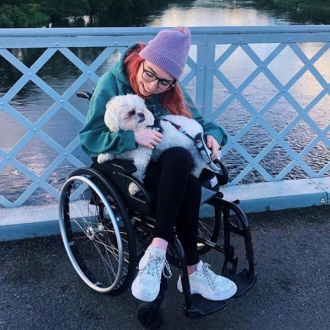 Georgia is cuddling her white dog on her knee. She is on a bridge with blue criss cross railings and the river behind her. She's wrapped up for the cold in a lilac beanie hat and green hoodie.