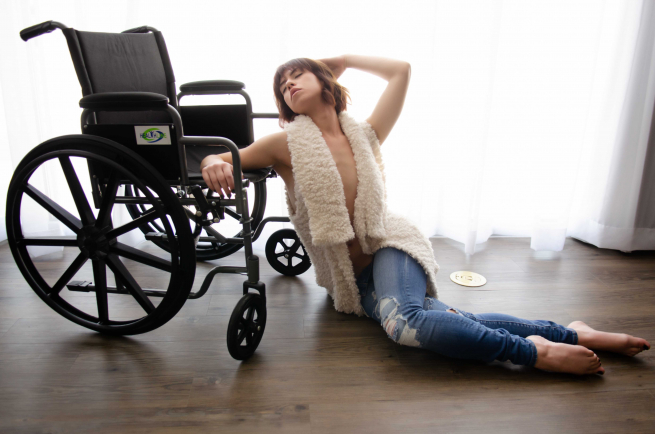 Josie is wearing jeans and a white sleeveless open top, revealing her bare arms and part of her chest. She is sitting on a wooden floor with her back and arm resting against her wheelchair.