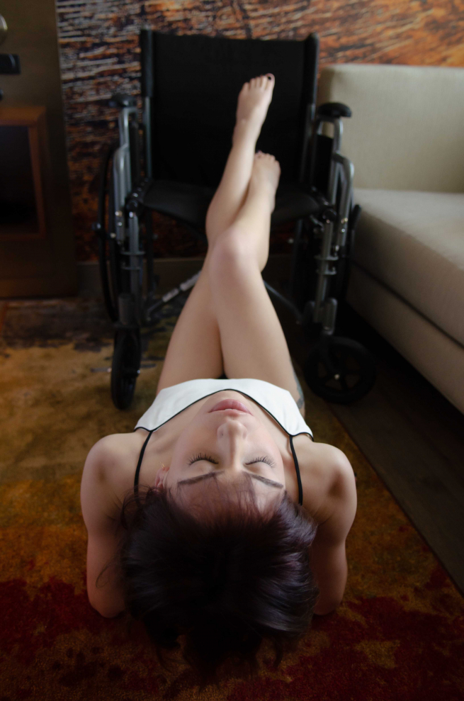 Josie is lying on her back on the carpet, she's wearing a silky white strappy top. Her legs are raised and rest together on her wheelchair. Her toenails are painted black and she has her head back and eyes closed. Her skin is pale white and she looks very elegant.