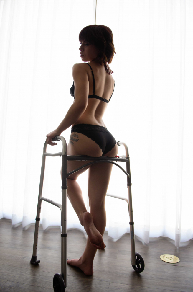 Josie is standing up in black underwear, leaning against a walking frame. Her brown hair is almost to her shoulders, she has pale skin and her nails are painted black. Josie has a tattoo on her hip, there is a white sheer curtain behind her and a wooden floor.