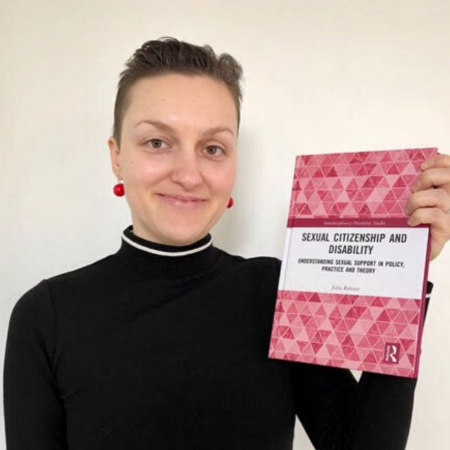 Julia is pictured wearing a black polo neck jumper and red drop earrings. She is holding a copy of her book, which has pink hexagons on the cover. She has short dark brown hair and is smiling at the camera.